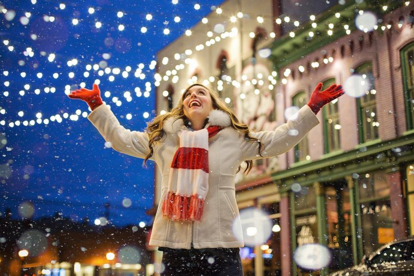 Girl in standing in snow and with lights around.